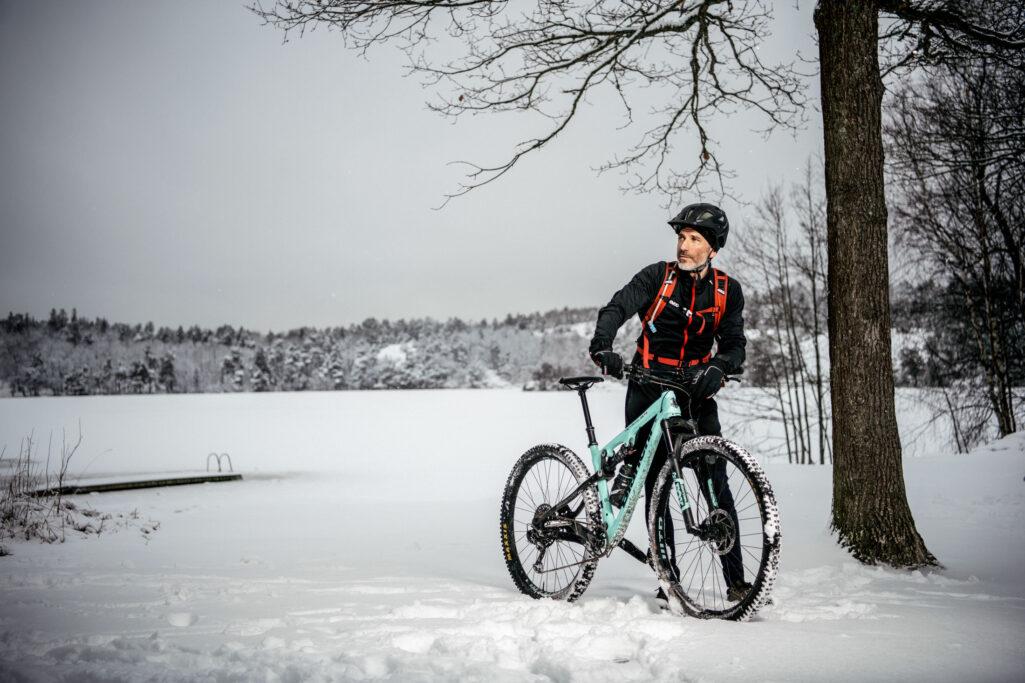 Jens Lapidus vid sin cykel i snölandskap
