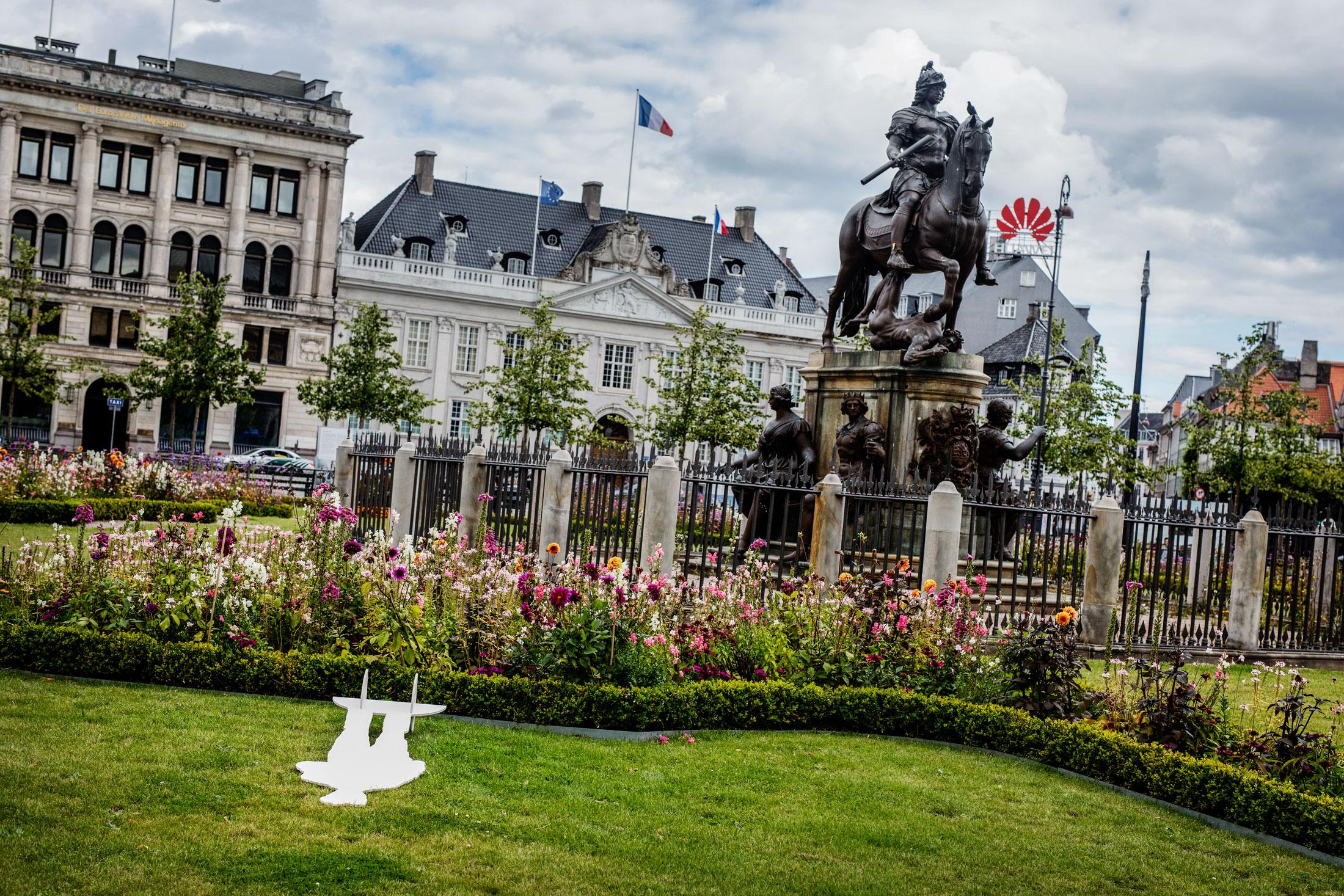 En fallen Strindbergsfigur vid statyn på Kongen nytorv.